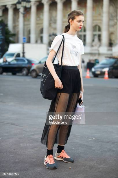 Model Maria Clara wears a Dior Sauvage white tshirt sheet black skirt/shorts and Nike shoes on July 3 2017 in Paris France