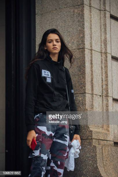 Model Maria Miguel wears a 'don't be the same' black hoodie and maroon/black camouflage military cargo pants after the Carolina Herrera show during...