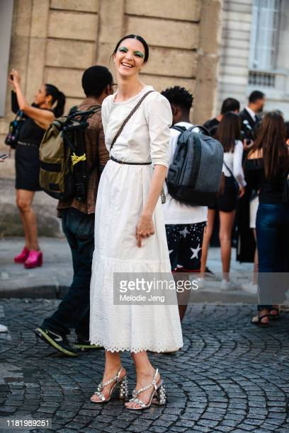 Model Mariacarla Boscono wears a white dress with silver studded heels after the Valentino show during Couture Fashion Week Fall/Winter 2019 on July...