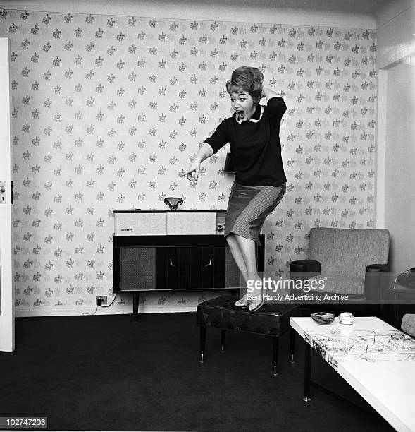 Model Marion Ryan standing on a footstool and pointing in alarm probably at a mouse 12th September 1961