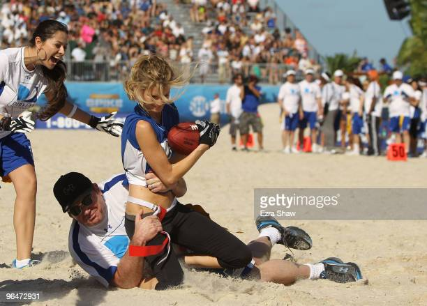 Model Marisa Miller is tackled by actor Tom Arnold at the Fourth Annual DIRECTV Celebrity Beach Bowl at DIRECTV Celebrity Beach Bowl Stadium South...