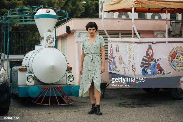 Model Marita Gogodze wears a green floral dress and black boots and poses in front of a toy train at the Tbilisi Circus during MercedesBenz Fashion...