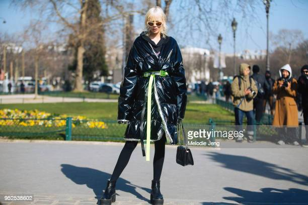 Model Marjan Jonkman wears yellow lucie Dries Van Noten sunglasses and a belted Jenneskens reflective puffer jacket on February 28 2018 in Paris...