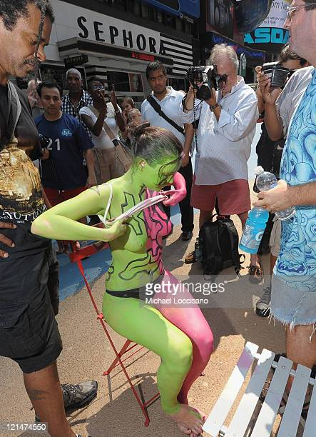 Model Marla Mera is body painted in the nude in Times Square on August 19 2011 in New York City