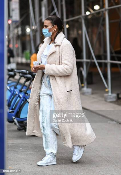 Model Marquita Pring is seen wearing a cream coat, white sweatshirt, tie dye pants and Nike sneakers outside the Christian Siriano show during New...