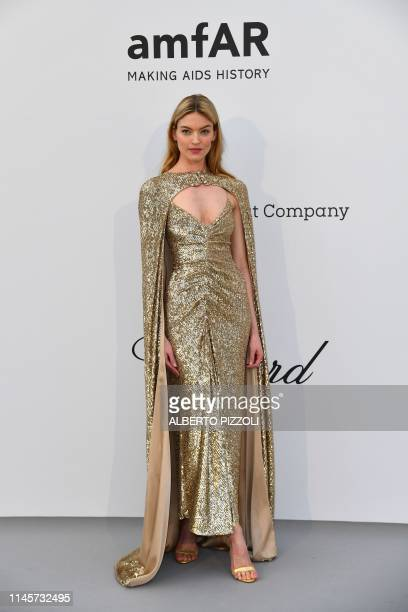 US model Martha Hunt poses as she arrives on May 23 2019 at the amfAR 26th Annual Cinema Against AIDS gala at the Hotel du CapEdenRoc in Cap...
