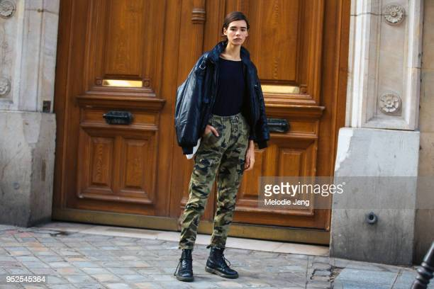 Model Martine Dirkzwager wears a brown leather jacket black tshirt cargo camouflage pants and black boots after the Sacai show on March 05 2018 in...