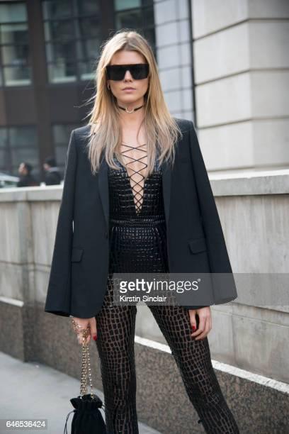 Model Maryna Linchuk wearing a Julien Macdonald jumpsuit Max Mara sunglasses El'Beu choker and a Saint Laurent jacket on day 2 of London Womens...