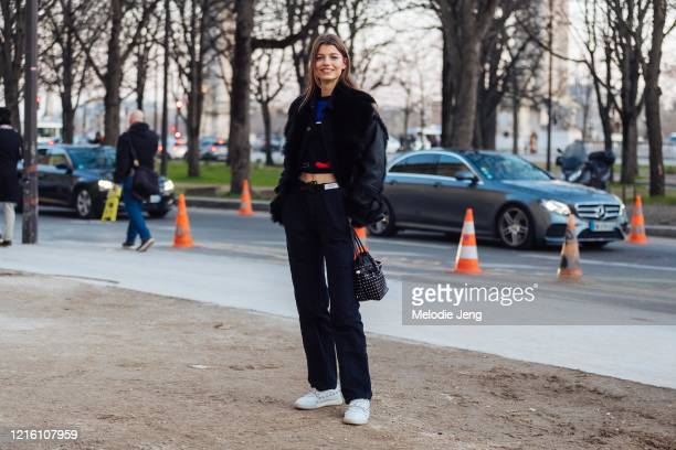 Model Mathilde Henning wears a black Iro Paris shearling jacket, croptop, black pants, studded bag, black pants, and white studded sneakers after the...