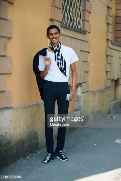 "Model Matthew Petersen wears a black and white striped Fendi scarf, black shirt, black pants, and black Adidas x Pharrell Williams ""human race""..."