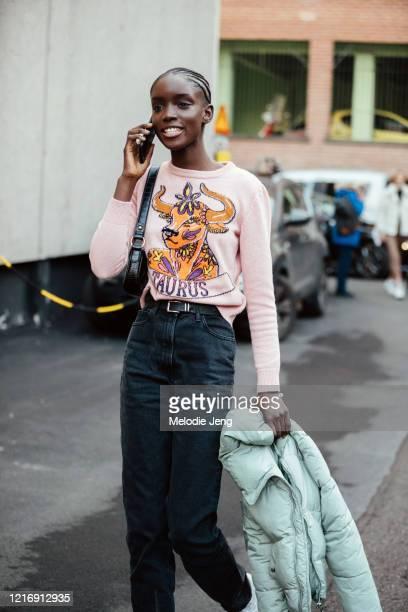 "Model Maty Fall talks on the phone and wears a ""Taurus"" horoscope Alberta Ferretti pink knit sweater and black jeans after the Alberta Ferretti show..."