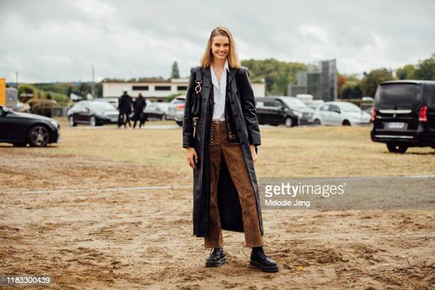 Model Maud Hoevelaken wears a long black leather trench coat white shirt brown suede pants and black boots after the Dior show during Paris Fashion...