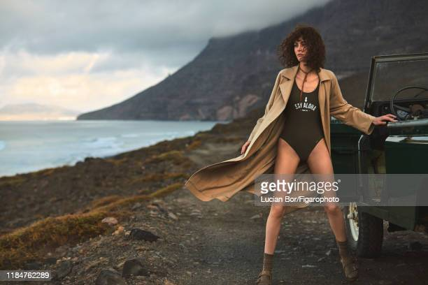 Model Maud Le Fort is photographed for Madame Figaro on November 30, 2017 in Lanzarote, Spain. Trenchcoat , swimsuit , cord , socks , sandals ....