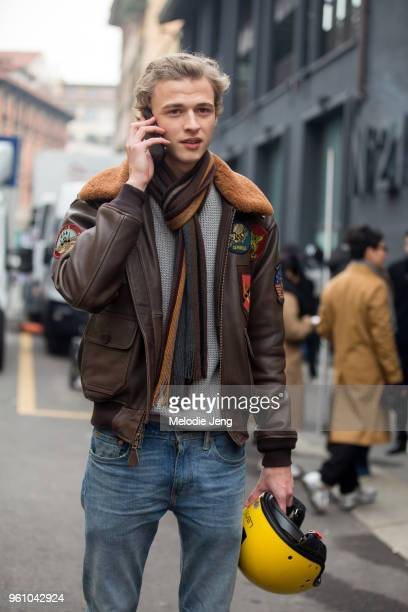 Model Max Barczak talks on the phone and wears a brown leather aviatorstyle jacket with patches a brown scarf gray top blue jeans and holds a yellow...