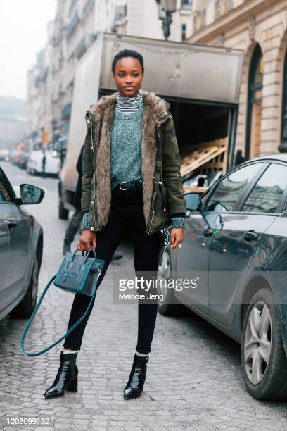 Model Mayowa Nicholas wears a green fur-lined camouflage coat, gray sweater, black pants, blue Celine bag, and black booties during Couture...