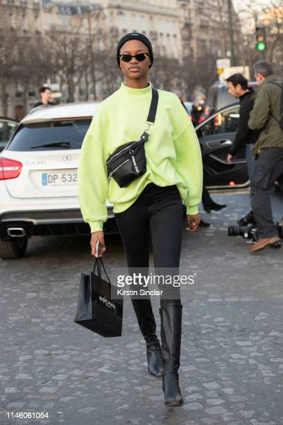 Model Mayowa Nicholas wears Fendi sunglasses, Steve Madden sling bag with skinny black jeans, knee high boots and a Neon green sweater on February...