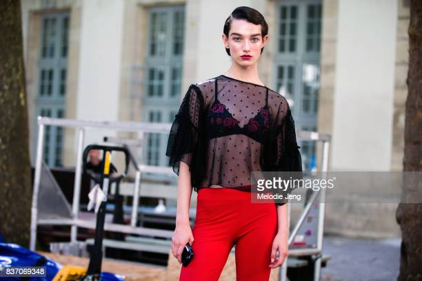 Model Mckenna Hellam wears a sheer lace top a bra with roses and red pants on July 04 2017 in Paris France