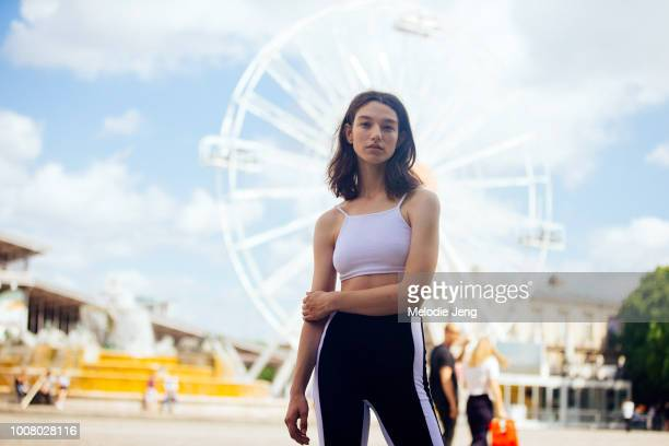 Model Mckenna Hellam wears a white cropped tanktop and black trackpants in front of a ferris wheel at Cite de la Musique after the Sacai show during...