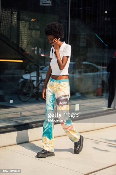 Model Metta Irebe talks on the phone and wears a white knit polo top, a vintage Roberto Cavalli Spring/Summer 2001 pants with illustration, and black...