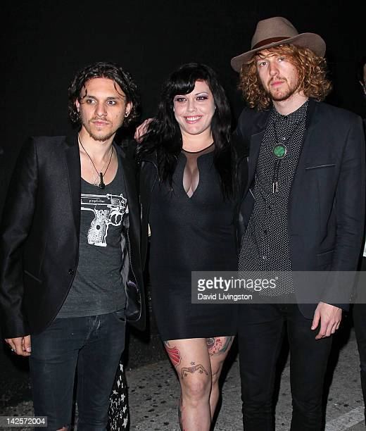 Model Mia Tyler poses with Click Clack Boom band members Jesse Kotansky and Nathaniel Hoho at the band's performance presented by Andrew Charles and...