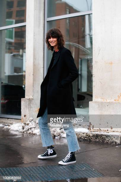 Model Mica Arganaraz wears a black coat blue jeans and black Converse sneakers on Day 3 of New York Fashion Week Fall/Winter 2017 on February 11 2017...