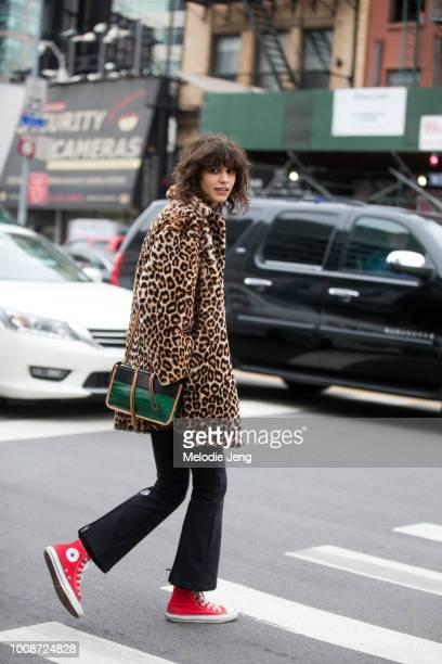 Model Mica Arganaraz wears a leopard fur coat green and black crocodile leather Proenza Schouler purse black flare pants and red Converse sneakers...