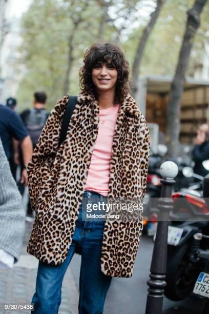 Model Mica Arganaraz wears a leopard fur jacket pink top and blue jeans during Paris Fashion Week Spring/Summer 2018 on September 28 2017 in Paris...