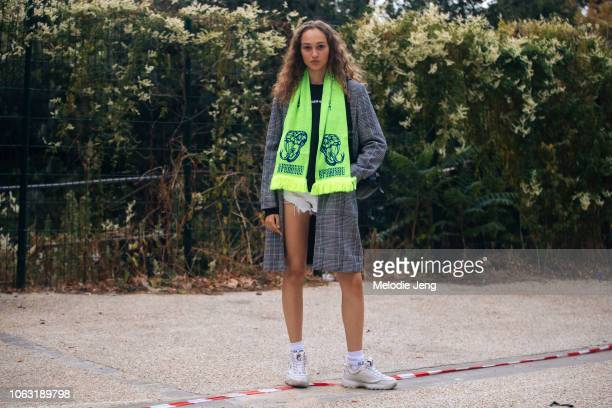 Model Michelle Gutknecht wears a green Kpodonou scarf gray coat Adidas black shirt and white Fila sneakers after the John Galliano show during Paris...