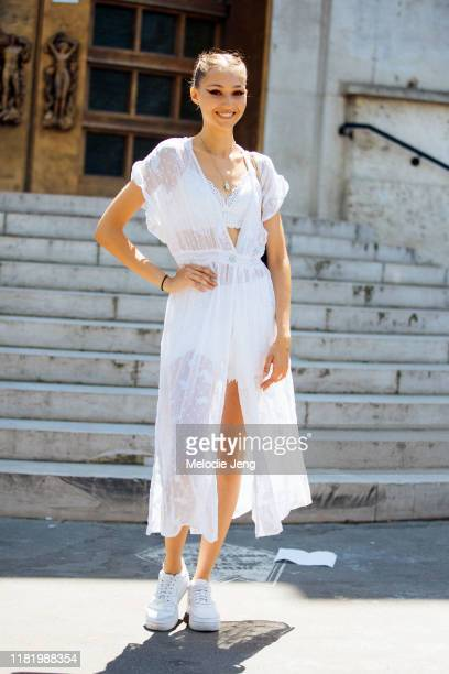 Model Michelle Gutknecht wears a white lace dress and white Nike Air Force 1 sneakers after the Elie Saab show during Couture Fashion Week...