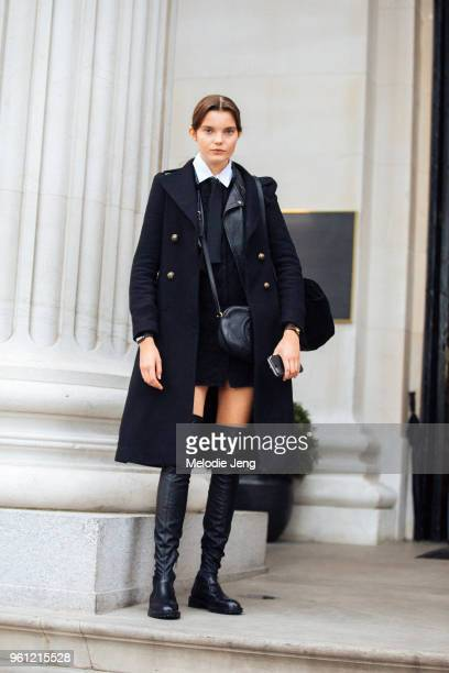 Model Michelle van Bijnen wears a preppy black peacoat, black top, black Gucci bag, black thigh-high boots during London Fashion Week Spring/Summer...
