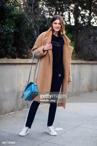 Model Milena Litvinovskaya wears a brown teddy bear coat blue Loewe puzzle bag a black shirt with russian text Tory Sport black joggers Tory Sport...