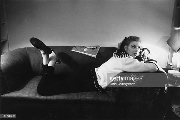 Model Miss G Ashley sprawls on a sofa as she models a 5 guinea sweater from Kenettas, Baker Street, London. The sweater has a yoke with a radiating...