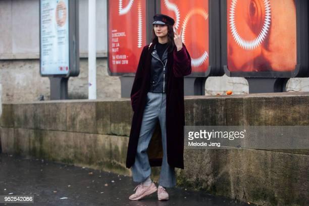 Model Mona Matsuoka throws a peace sign and wears a Ruslan Baginskiy black wool baker boy cap a long plum velvet coat a black leather jacket gray...