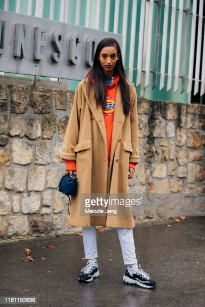 Model Mona Tougaard wears a camel coat, red Dickies hoodie, white jeans, small red Loewe bag, and black and white sneakers after the Loewe show...