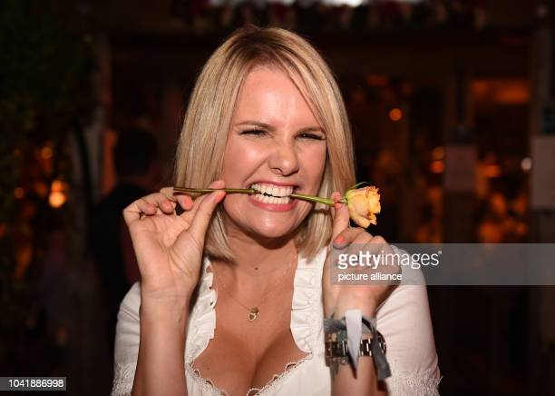 Model Monica Ivancan poses with a rose at the Kaeferzelt beer tent on the Oktoberfest in MunichGermany 21 September 2016 The 183th Wiesn take place...