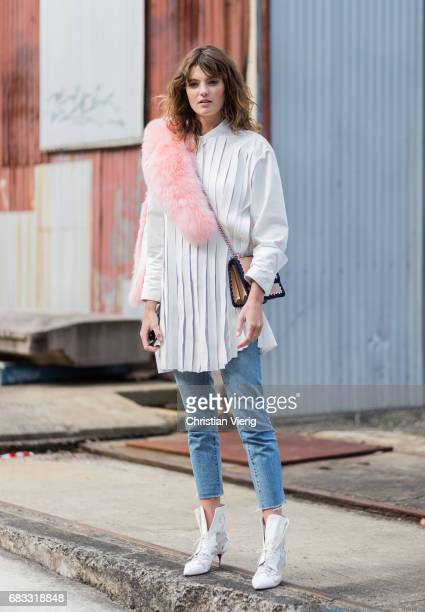 Model Montana Cox wearing a white blouse skinny denim jeans boots pink fake fur scarf at day 2 during MercedesBenz Fashion Week Resort 18 Collections...