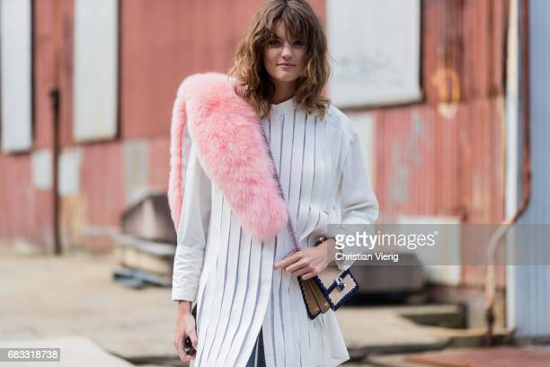 Model Montana Cox wearing a white blouse skinny denim jeans pink fake fur scarf at day 2 during MercedesBenz Fashion Week Resort 18 Collections at...