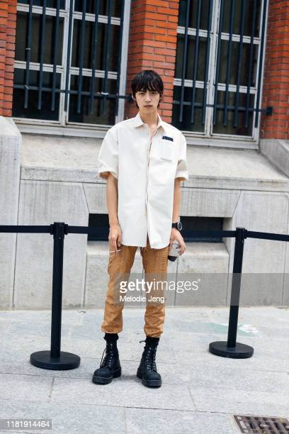 Model Na wears a white boxy Jil Sander top, light brown pants, and black chunky sneakers after the Jil Sander show during Paris Fashion Week Men's...
