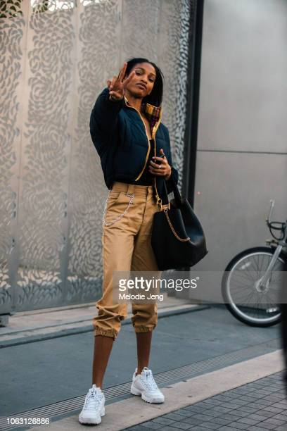 Model Naomi Chin Wing throws a peace sign and wears a blue cropped puffer jacket cropped khaki pants black bag and white Fila sneakers after the...
