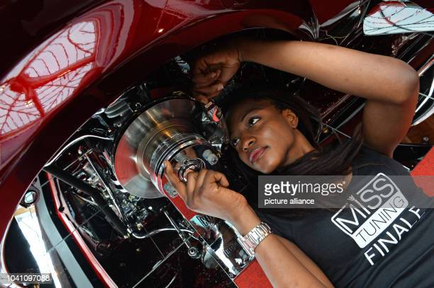 Model Naomi Sode poses under a 'tuned' Opel KadettC Coupe during a press tour of Tuning World Bodensee in FriedrichshafenGermany 03 May 2013The...