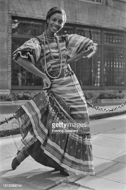 Model Naomi wearing a long dress with flamenco-style sleeves and horizontal stripes, UK, 25th October 1973.
