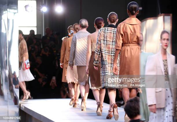Model Natalia Vodianova is reflected as she walks the catwalk during the Burberry London Fashion Week SS19 show held at The South London Mail Centre