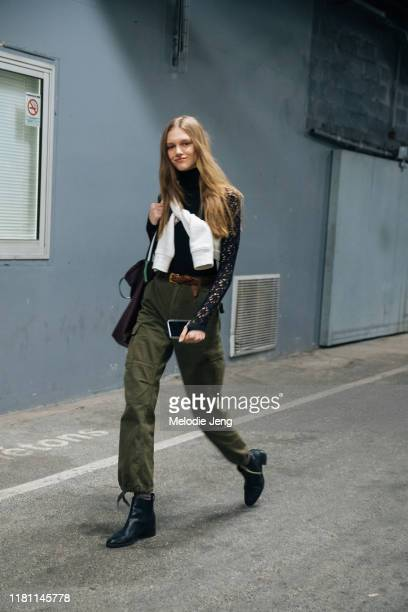Model Natalie Ogg wears a black lace top white sweatshirt tied across her chest green militarystyle pants and black booties after the OffWhite show...