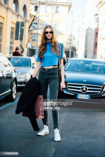 Model Natalie Ogg wears a blue tshirt black jeans and white JW Anderson x Converse sneakers after the Etro show on Day 3 Milan Fashion Week...
