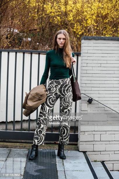 Model Natalie Ogg wears a green top white Dries Van Noten swirl pants black boots after the Balmain show during Paris Fashion Week Fall/Winter 2019...