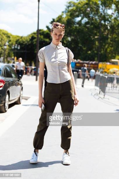 Model Natalie Ogg wears a white shirt green pants and white sneakers after the Chanel show during Couture Fashion Week Fall/Winter 2019 on July 02...