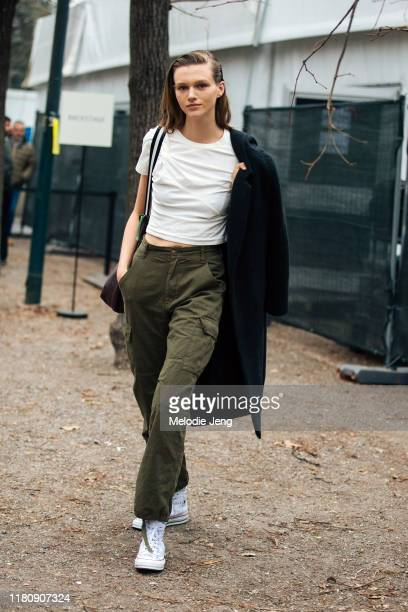 Model Natalie Ogg wears a white tshirt black jacket green pants and white JW Anderson x Converse sneakers after the Roberto Cavalli show on Day 4...