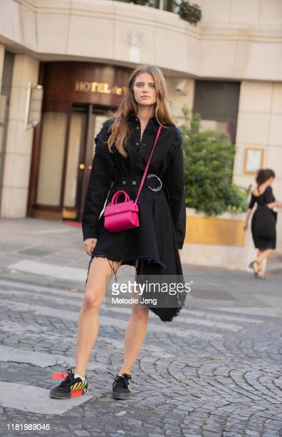 Model Nataliya Bulycheva wears a black belted asymmetrical dress, pink Givenchy bag, and black Off-White sneakers after the Zuhair Murad show during...