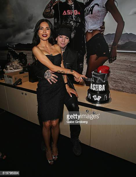 Model Nathalia Henao and her husband guitarist Dj Ashba of SixxAM cut a cake during the grand opening of their Ashba Clothing Store at the...