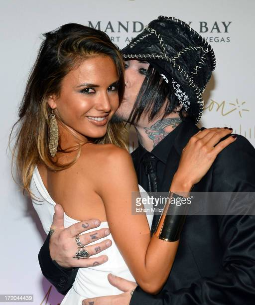 Model Nathalia Henao is kissed by guitarist Dj Ashba of Guns N' Roses as they arrive at the world premiere of Michael Jackson ONE by Cirque du Soleil...
